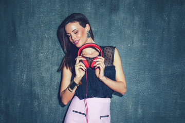 Nuanced stylish woman holding headphones at wall