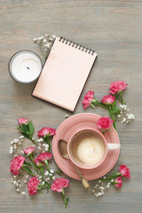 Cup of creamy coffee, notepad and flowers