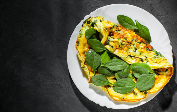 omelet with spinach in white plate on Dark grey black slate background