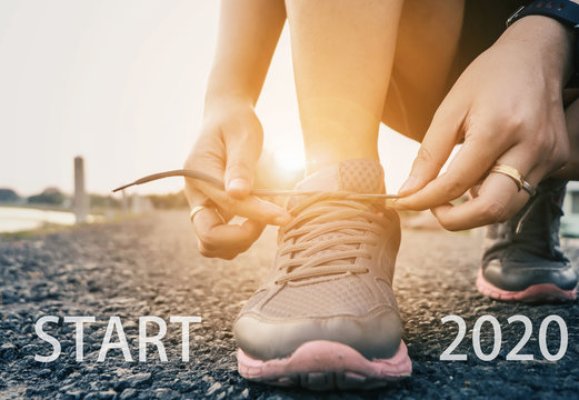 2020 the start into the new year.sports background. legs of runner feet running on road