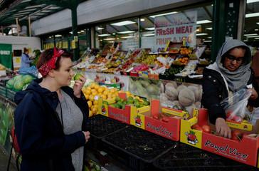 Katarzyna Kociniewska, 36, doctoral student, checks fruits at a street market in Nottingham