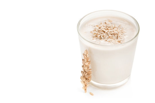 Glass of oat milk and grains on top