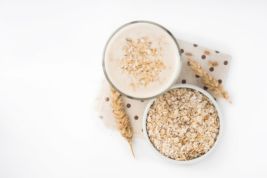 Glass of oat milk and grains in white bowl