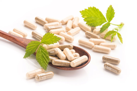 Herbal medical capsule with green leaf isolated