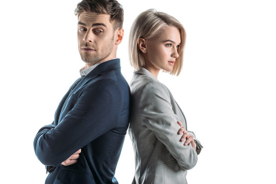 attractive businesswoman and good-looking businessman standing back to back with crossed arms isolated on white