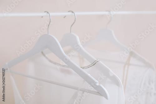 19b73d295f9 White dresses on a hanger. Minimalism concept. Set of women wedding dresses  on a