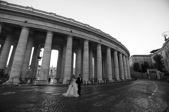 Beautiful wedding couple posing on street near old historic columns