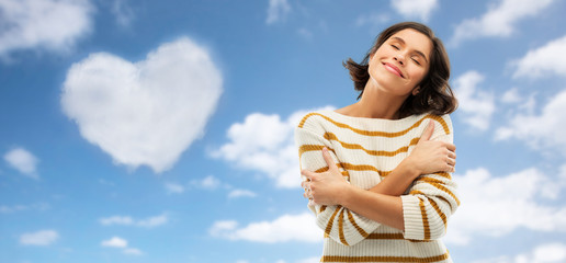 valentine's day, love people concept - happy pleased young woman in striped pullover with closed eyes hugging herself over blue sky and cloud in shape of heart background