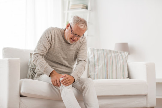 people, health care and problem concept - unhappy senior man suffering from knee ache at home