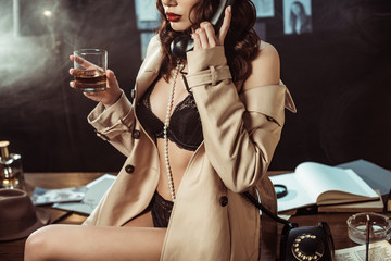 Partial view of sexy woman in black lingerie and trench coat holding glass of cognac while talking on telephone
