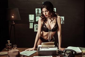 Sexy woman in black underwear standing near table with typewriter in office