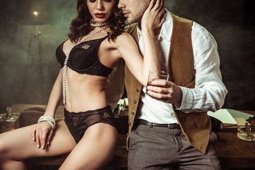 Cropped view of sexy woman in black lingerie sitting on wooden table and flirting with detective in office