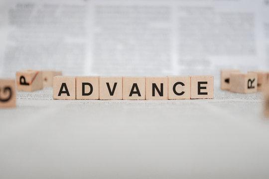 Advance Word Written In Wooden Cube - Newspaper