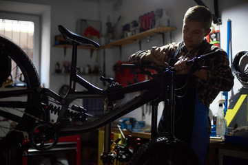 Male mechanic working in bicycle repair shop, serviceman repairing modern bike using special instrument, wearing protective workwear and gloves