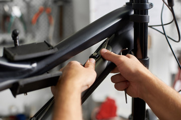Cropped shot of serviceman working in bicycle repair shop, bicyclist fixing bike using special tool