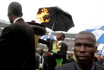 President Emmerson Mnangagwa shelters under an umbrella as he lights the country's Independence flame during anniversary celebrations in Harare