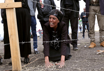 A family member of the Ethiopian Airlines Flight ET302 plane crash victims mourns at the fenced-off accident site during the final mourning day to mark the 40th day in Gara Boka village, near Bishoftu town, Southeast of Addis Ababa