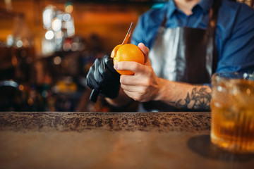 Male bartender cleans orange at the bar counter