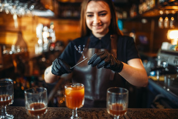 Female bartender holding a glass with coctail