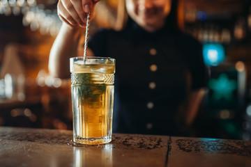 Female barman stir the drink in a glass