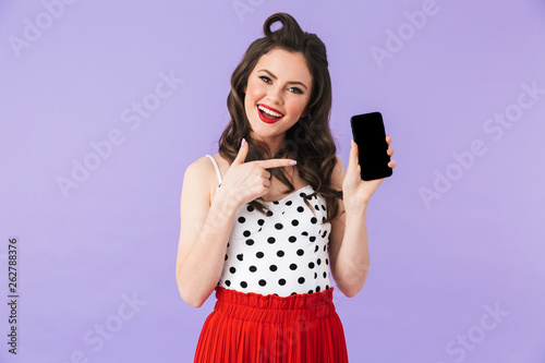 d28a9dcd3 Portrait of young pin-up woman 20s in retro polka dot dress smiling and  holding