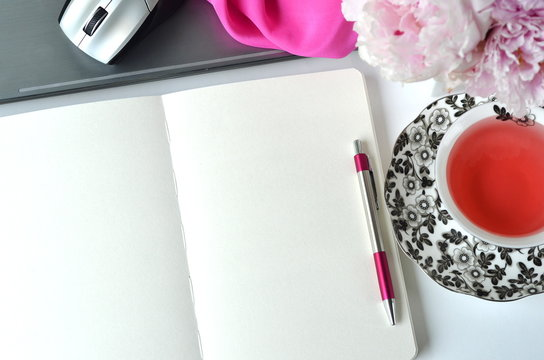 Elegant styled feminine desktop - relaxation, reading, creative writing, learning and journaling concept - with pink peonies, fruit tea and stylish stationery. Working from home.