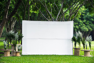 Blank white empty space big screen advertising banner fabric mock up template in outdoor green tropical garden public park.