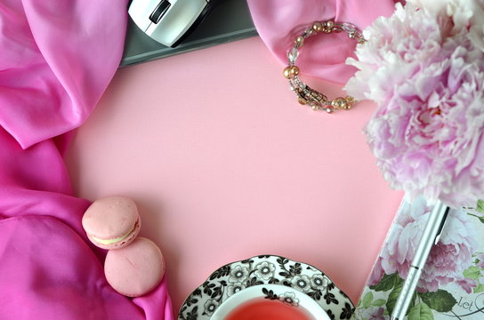 Elegant styled feminine desktop - relaxation, reading, creative writing, learning and journaling concept - with pink peonies, fruit tea and stylish stationery