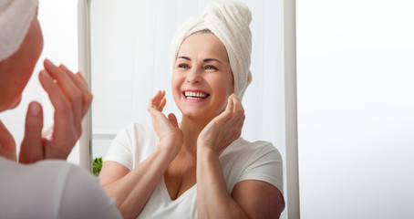 Smiling middle aged woman satisfied with her nature beauty. Cosmetic facial care concept