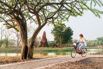 Female traveler weared light summer clothes and hat have early morning bicycle walk in Ayutthaya historical park, Thailand