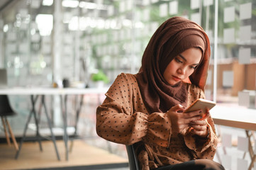 Muslim female using mobile phone and sitting on office room.