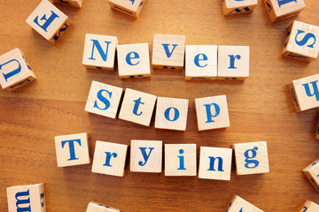 Never stop trying. Conceptual image with the text made from wooden cubes on a desk