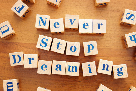 Never stop dreaming. Conceptual image with the text made from wooden cubes on a desk