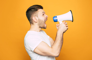Listen! A man on the photo is using a megaphone to  raise his voice up for talking to somebody who is on the other side of he