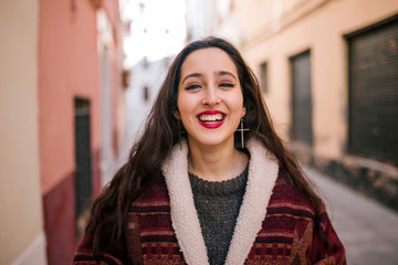 girl with coat smiles happily on a pretty street of a city in europe