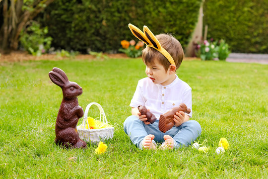 Cute little baby boy with bunny ears eating chocolate Easter bunnies sitting on green grass outside in the spring garden with basket of easter eggs looking at big chocolate rabbit. Childhood