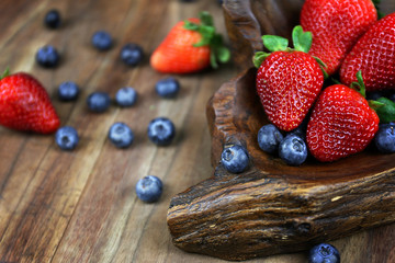 Display of Fresh Strawberries and Blueberries in Rustic Wooden Bowl