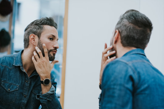 Reflection in mirror of handsome stylish male checking beard in salon