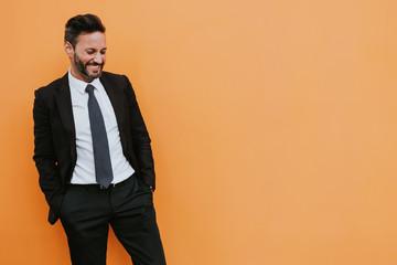 Adult handsome elegant businessman in formal suit looking at camera near orange wall