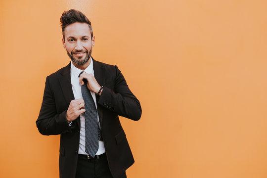 Adult handsome elegant businessman in formal suit adjusting tie and looking at camera near orange wall