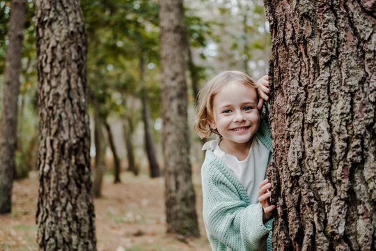 Positive child looking at camera behind wood in park on blurred background