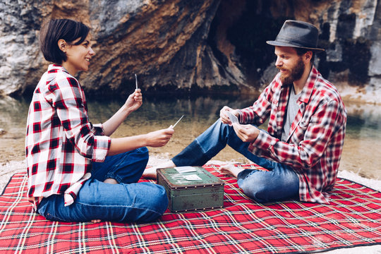 Side view of man and woman in plaid shirts playing cards on plaid having picnic on shore of lake in cliffs