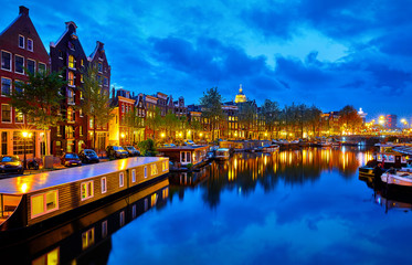 Fototapete - Evening town Amsterdam in Netherlands on bank river canal Amstel with shining window. Panorama landscape brown house over water reflection.