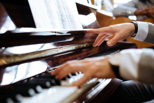 Crop side view of man hands playing piano in a music studio