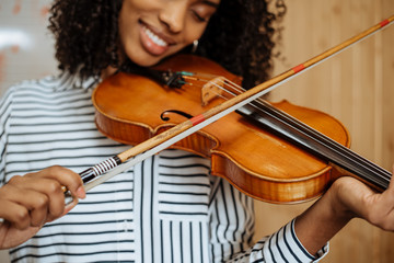 Young woman playing violin with writing board on the background in music studio