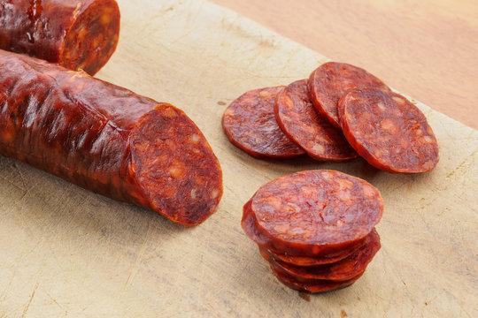 Iberian chorizo, Spanish chorizo or Spanish sausage cut into slices on a wooden board