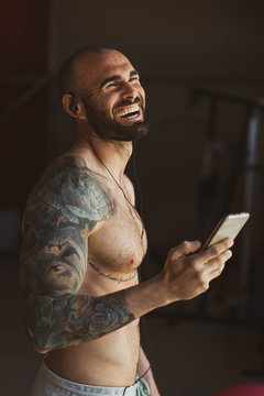 Side view of handsome tattooed male with smartphone laughing and listening to music while standing in modern gym during training