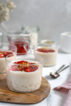 Healthy vegan dairy free dessert - tapioca pearls pudding with coconut milk and strawberry chia jam close up, served in glass jar