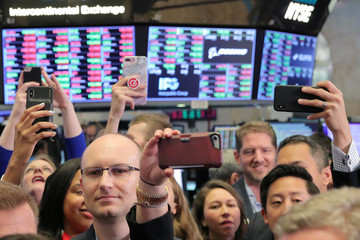 Guests use their phones during the Pinterest Inc. IPO on the floor of the NYSE in New York
