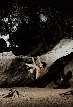 Muscular man practicing rock climbing among large rocks in a forest at sunset